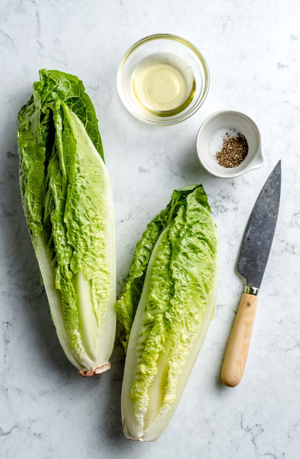 Grilled lettuce ingredients arranged on a white & grey marble surface - two heads of fresh romaine lettuce, avocado oil, kosher salt, & ground black pepper. A pairing knife rests on the surface next to the ingredients.