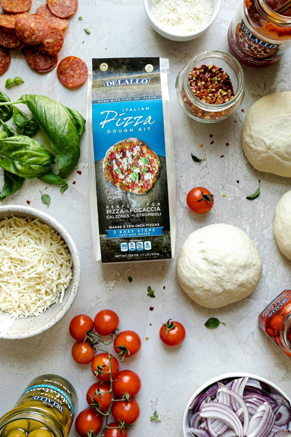 Grilled Pizza Night toppings arranged on a creamy cement surface – DeLallo pizza dough kit, pizza dough balls, pepperoni, pizza sauce, tomatoes, cheese, sliced onion, castelvetrano olives, tomatoes, etc.