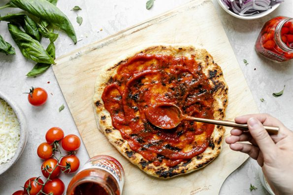 How to grill pizza, Step 5: Grilled pizza assembly. A woman's hand shown spreading pizza sauce over par-grilled crust with a spoon. The crust sits atop a wooden pizza peel, surrounded by fresh basil, cherry tomatoes, cheese, peppers, & sliced red onion.
