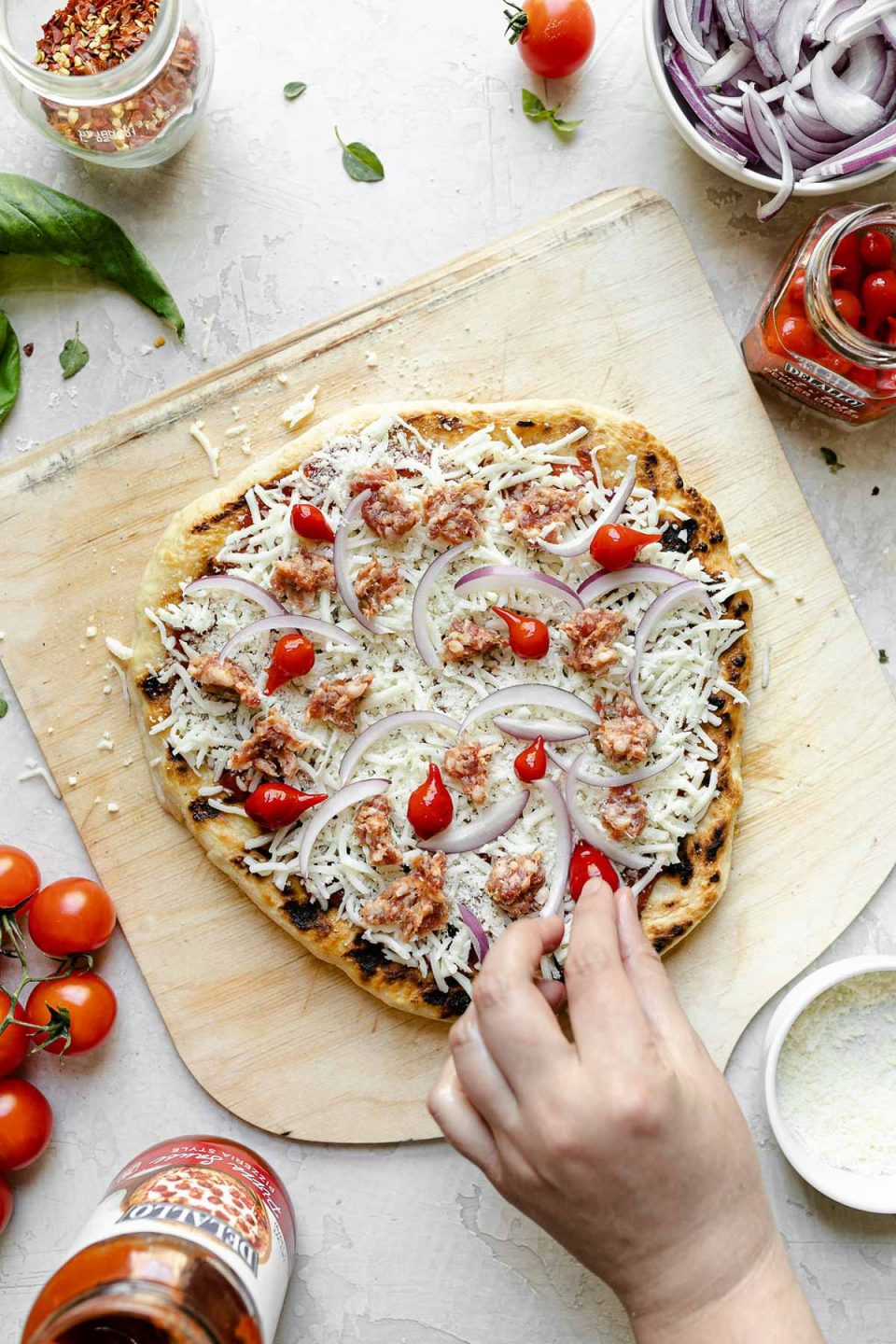 A woman's hand shown topping pizza with cheese, sausage, onions, & sweetie drop peppers. The crust sits atop a wooden pizza peel, surrounded by fresh basil, cherry tomatoes, cheese, peppers, & sliced red onion.