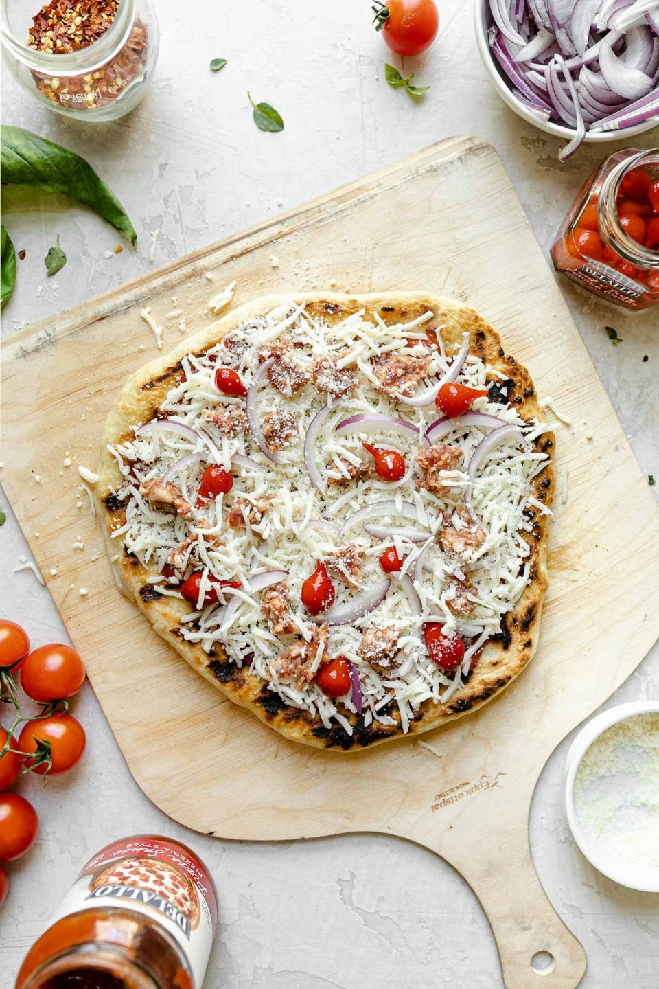 A par-grilled pizza topped with cheese, sausage, onions, & sweetie drop peppers. The crust sits atop a wooden pizza peel, surrounded by fresh basil, cherry tomatoes, cheese, peppers, & sliced red onion.
