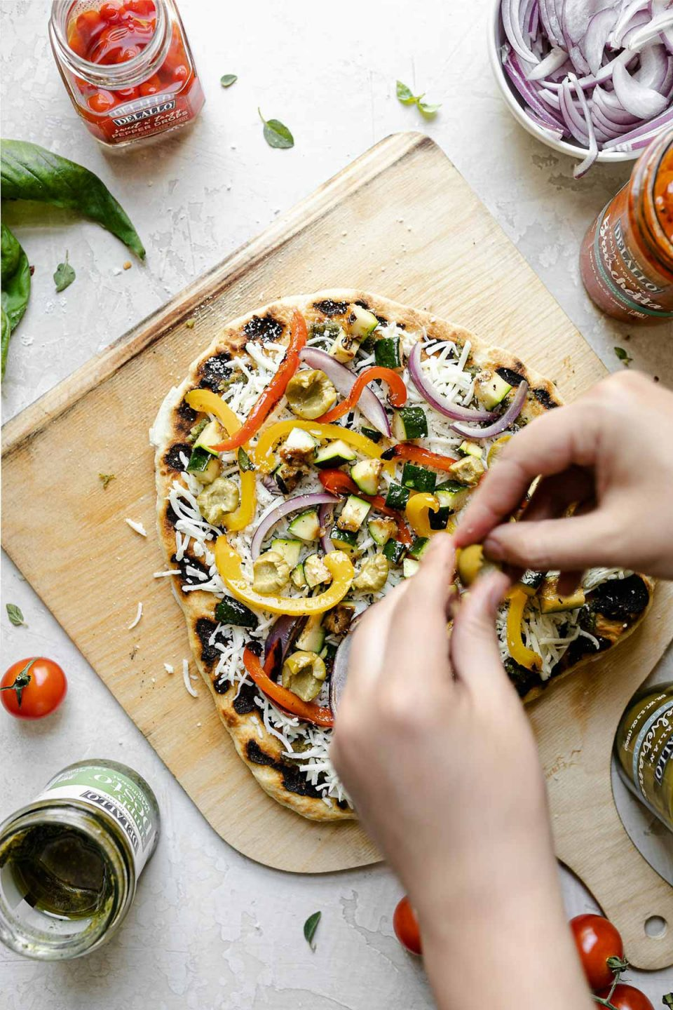 A woman's hand shown topping pizza with cheese, castelvetrano olives & grilled vegetables. The crust sits atop a wooden pizza peel, surrounded by fresh basil, cherry tomatoes, cheese, peppers, & sliced red onion.
