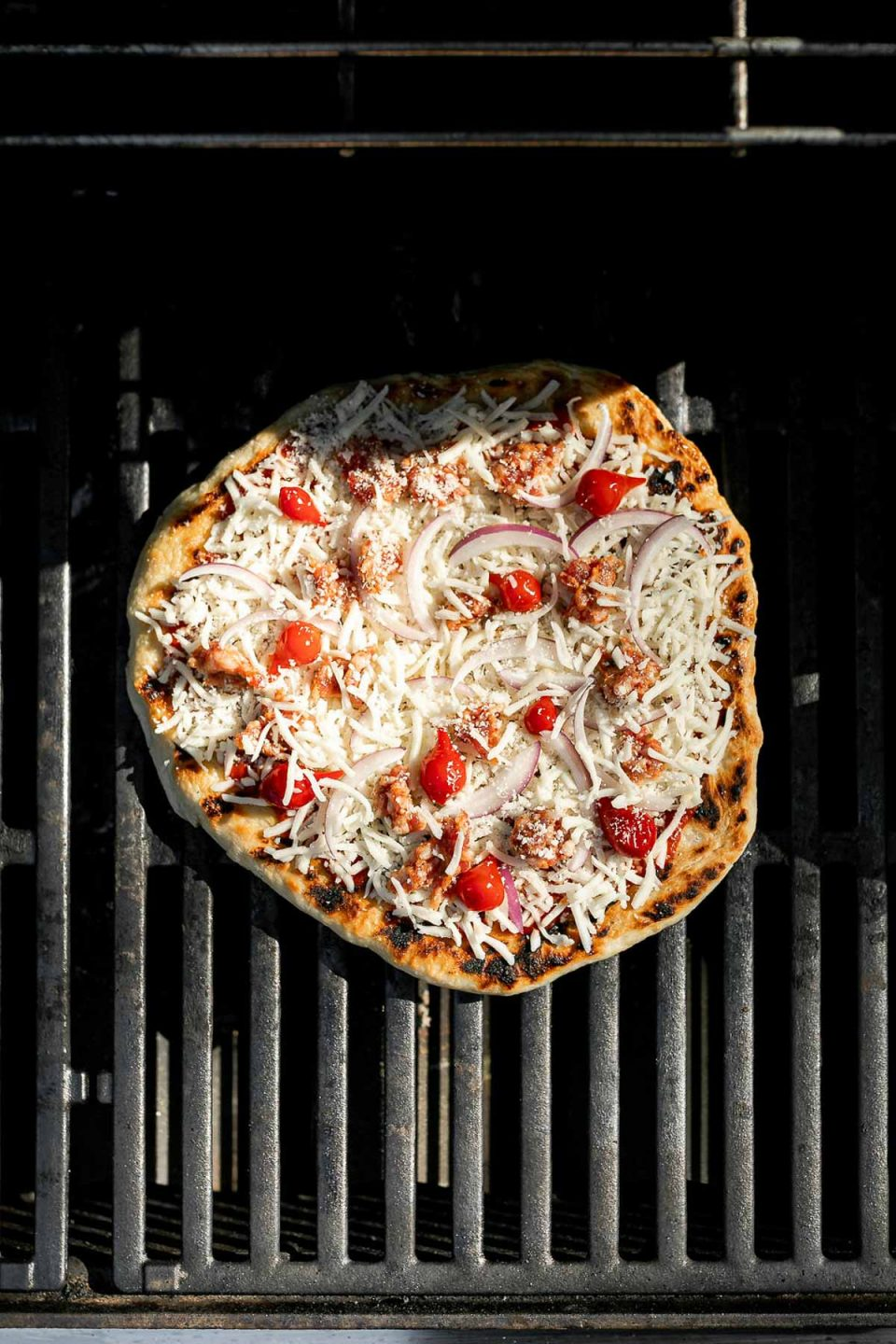 Assembled pizza shown on grill grates over direct heat.