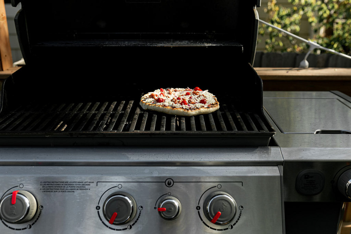 How to grill pizza, Step 6: Assembled pizza shown on grill grates over direct heat.