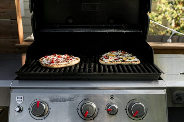 How to grill pizza, step 6: 2 assembled pizzas shown on grill grates. One pizza is finishing in the indirect heat zone while the other pizza is grilling in the direct heat zone.