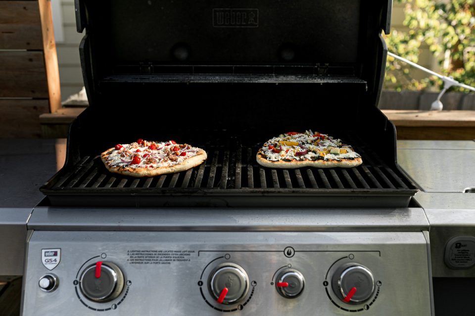 2 grilled pizzas on a Weber Genesis II propane grill. The pizzas are grilled with the 2-zone method, one is over direct heat & one is in an indirect heat zone.