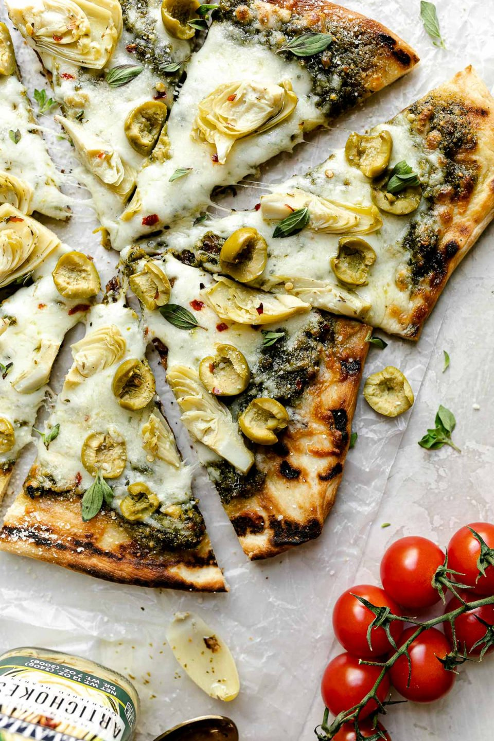 Grilled pizza topped with pesto, artichokes, & castelvetrano olives. The pizza sits atop a white surface, surrounded by fresh basil, tomatoes, & a jar of DeLallo castelvetrano olives.