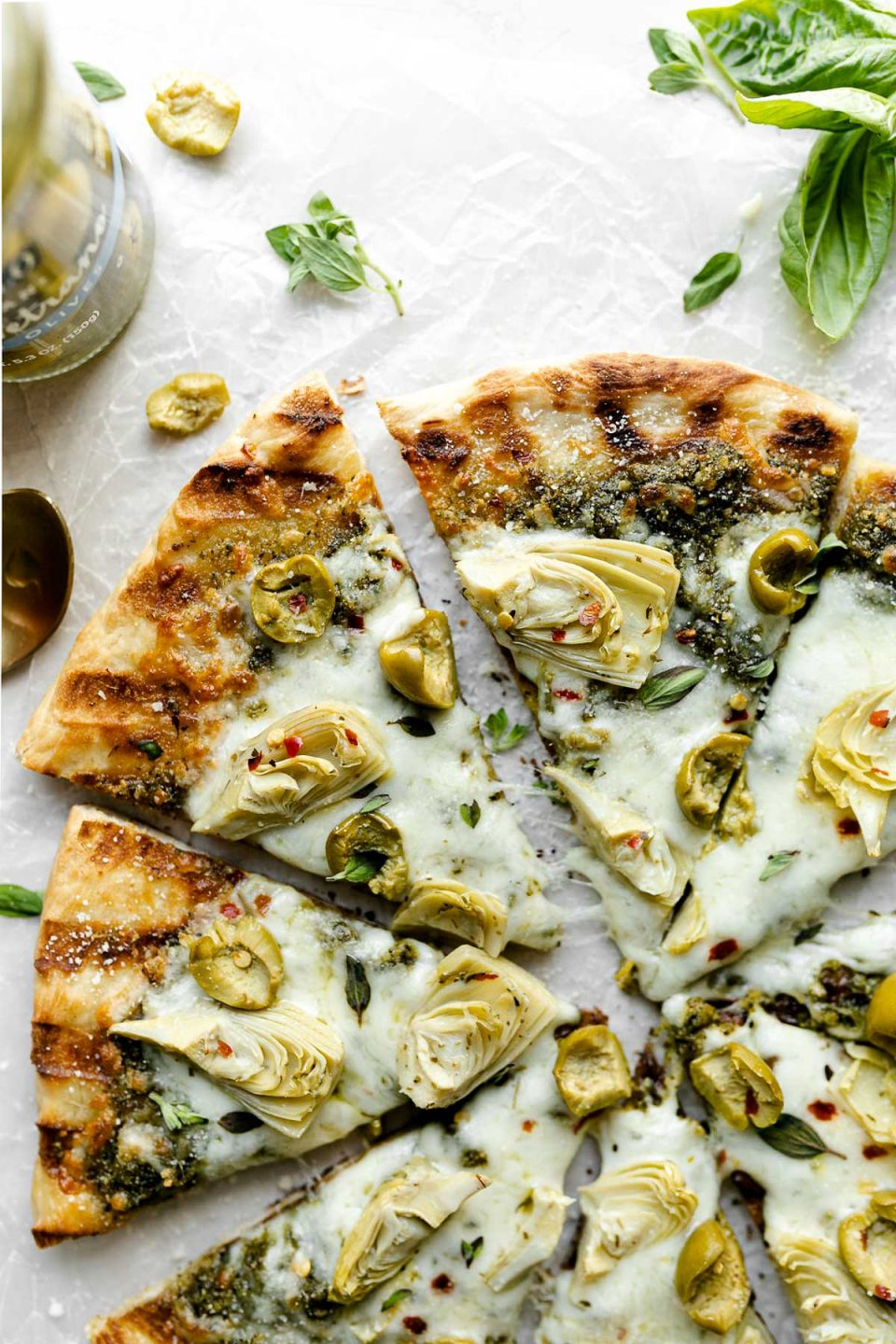 Grilled pizza topped with pesto, artichokes, & castelvetrano olives. The pizza sits atop a white surface, surrounded by fresh basil & a jar of DeLallo castelvetrano olives.