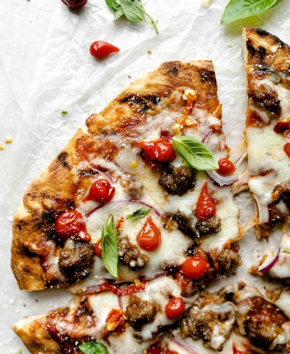 Grilled pizza topped with cheese, Italian sausage, sweetie drop peppers, & fresh basil leaves. The pizza sits atop a white surface, surrounded by fresh basil leaves.