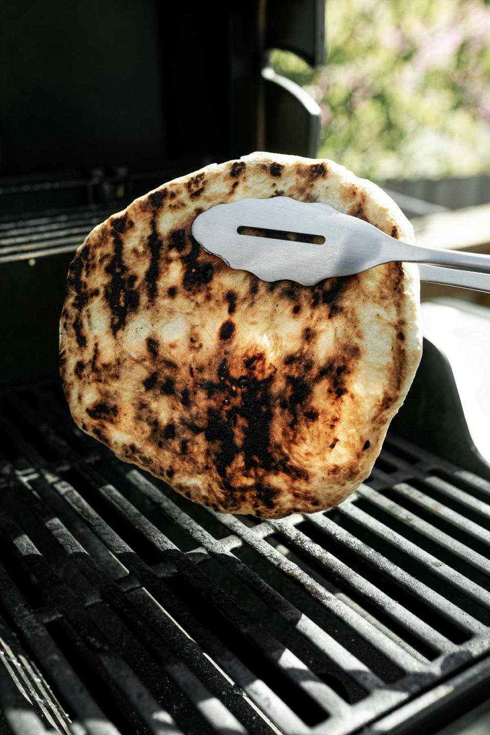 How to grill pizza, Step 4: Grilling tongs holding up par grilled pizza crust over grill grates, revealing perfectly grilled bottom.