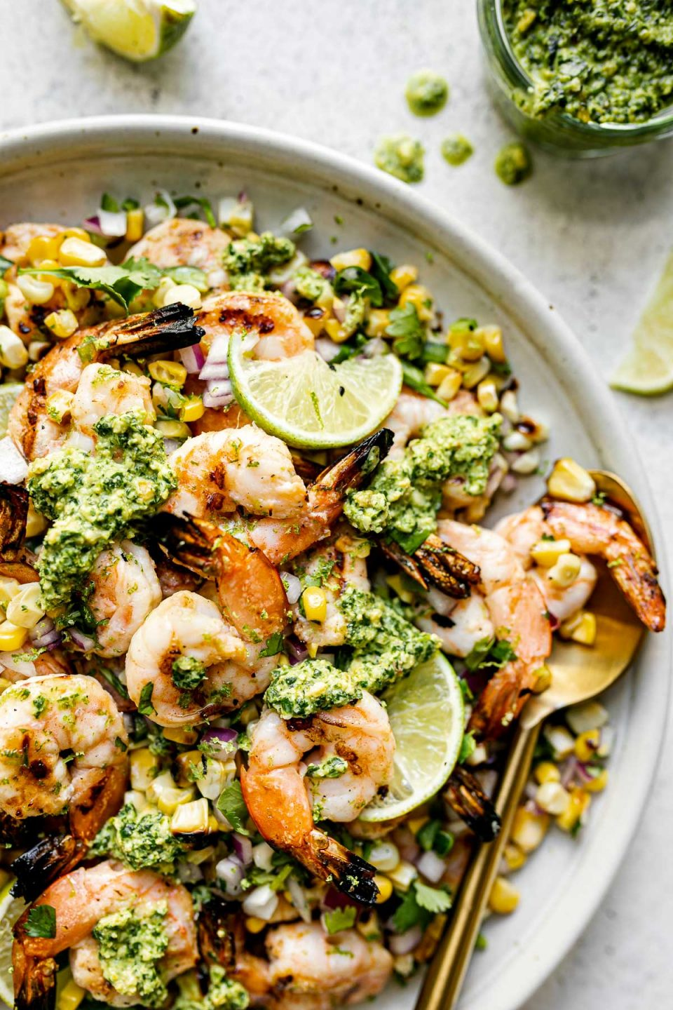 A close up of zesty grilled shrimp with jalapeño pesto & grilled corn salsa on top of a white ceramic plate & garnished with lime wedges. A gold serving spoon rests on the plate with a scoop of shrimp, corn salsa, & pesto. The plate sits atop a light gray & white surface, next to a small jar of jalapeño pesto, & a couple of squeezed lime wedges.