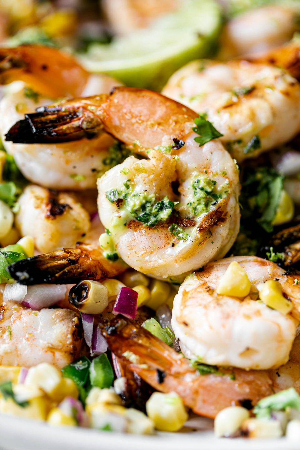 A close up of zesty grilled shrimp with jalapeño pesto & grilled corn salsa on top of a white ceramic plate & garnished with lime wedges.