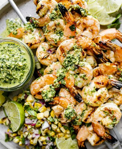 A close up of four zesty grilled shrimp skewers with jalapeño pesto & grilled corn salsa stacked on top of a gray speckled ceramic plate & garnished with lime wedges. A small jar of jalapeño pesto also sits on the plate ready for dipping or drizzling. The plate sits atop a light gray & white surface.