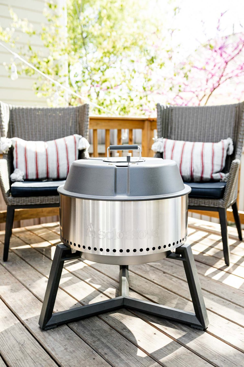 A Solo Stove Grill sits on top of a wooden deck with the lid close. Two gray patio chairs are set up behind the grill in the background, each with a red & white striped lumbar pillow on top of them.