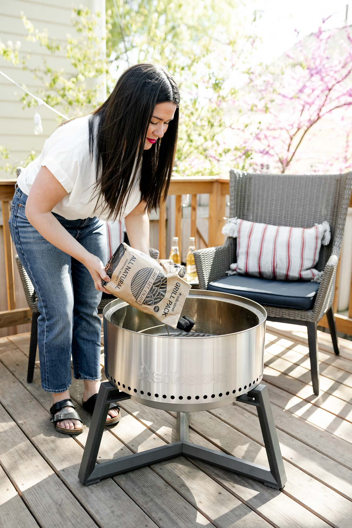 Jess of Plays Well With Butter setting up her Solo Stove Grill by filling with their all natural charcoal. Two gray patio chairs are set up behind the grill in the background, each with a red & white striped lumbar pillow on top of them. There is a small side table in between the two chairs with two Miller High Life beers on top.