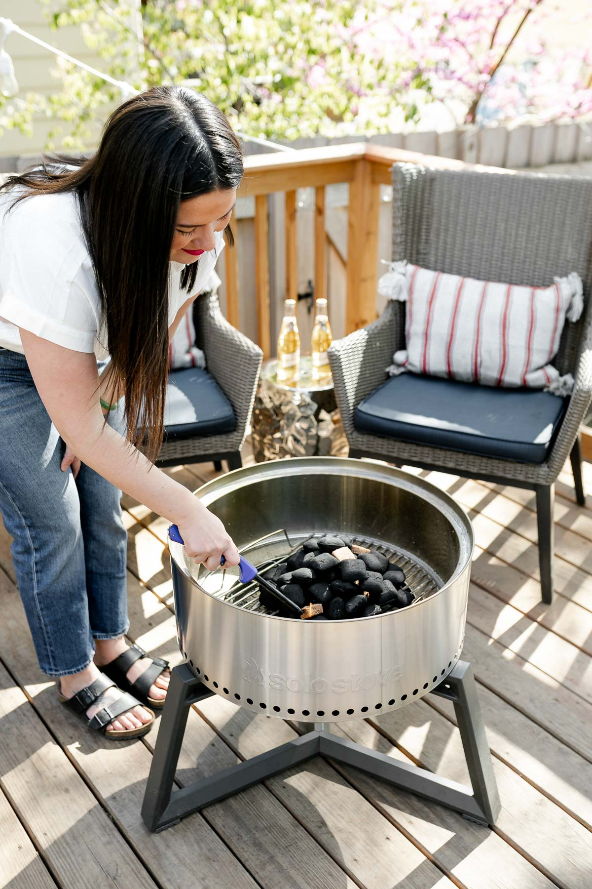 Jess of Plays Well With Butter lighting the all-natural charcoal inside her Solo Stove Grill with a long-handled lighter. Two gray patio chairs are set up behind the grill in the background, each with a red & white striped lumbar pillow on top of them. There is a small side table in between the two chairs with two Miller High Life beers on top.