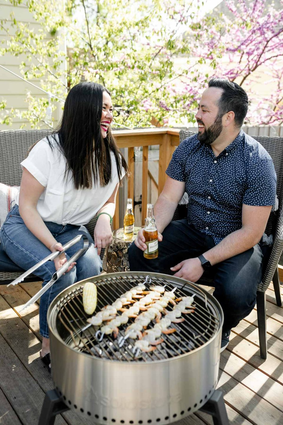 Jess of Plays Well With Butter holds a set of grill tongs while grilling grilled shrimp skewers & a cob of sweet corn on a Solo Stove Grill alongside her husband Chris. Both Jess & Chris are seated behind the grill looking at each other, laughing, while Chris holds a beer in one hand. They are seated outside on their deck.