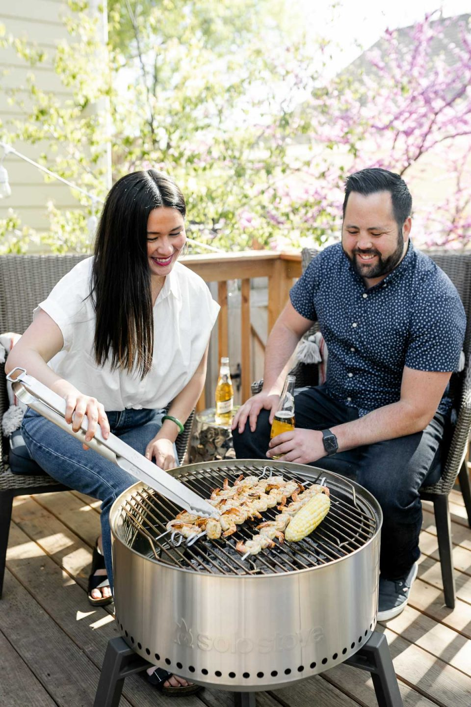 Jess of Plays Well With Butter is grilling grilled shrimp skewers & a cob of sweet corn on a Solo Stove Grill alongside her husband Chris. Both Jess & Chris are seated behind the grill looking at the grill, smiling, while Chris holds a beer in one hand. They are seated outside on their deck.