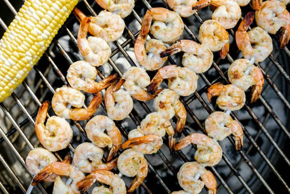 A close up of four grilled shrimp skewers and a cob of sweet corn grilling on top of a Solo Stove Grill. The grilled shrimp are becoming opaque & developing a golden brown char from the grill.