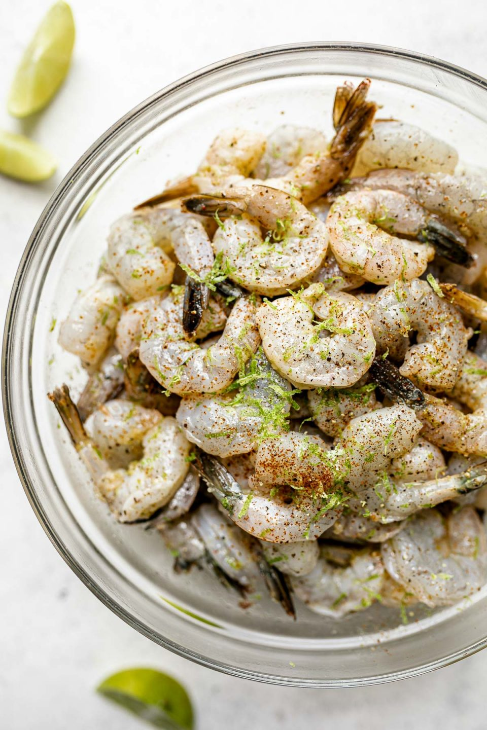 A close up of raw jumbo shrimp in a large glass mixing bowl, marinating in a zesty garlic & lime marinade. The bowl sits atop a gray & white textured surface and is surrounded by lime wedges..