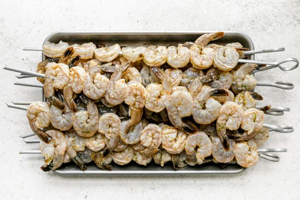 Multiple skewers of zesty marinated jumbo shrimp are stacked on top of an aluminum baking sheet. The baking sheet sits on top of a white & light gray textured surface.