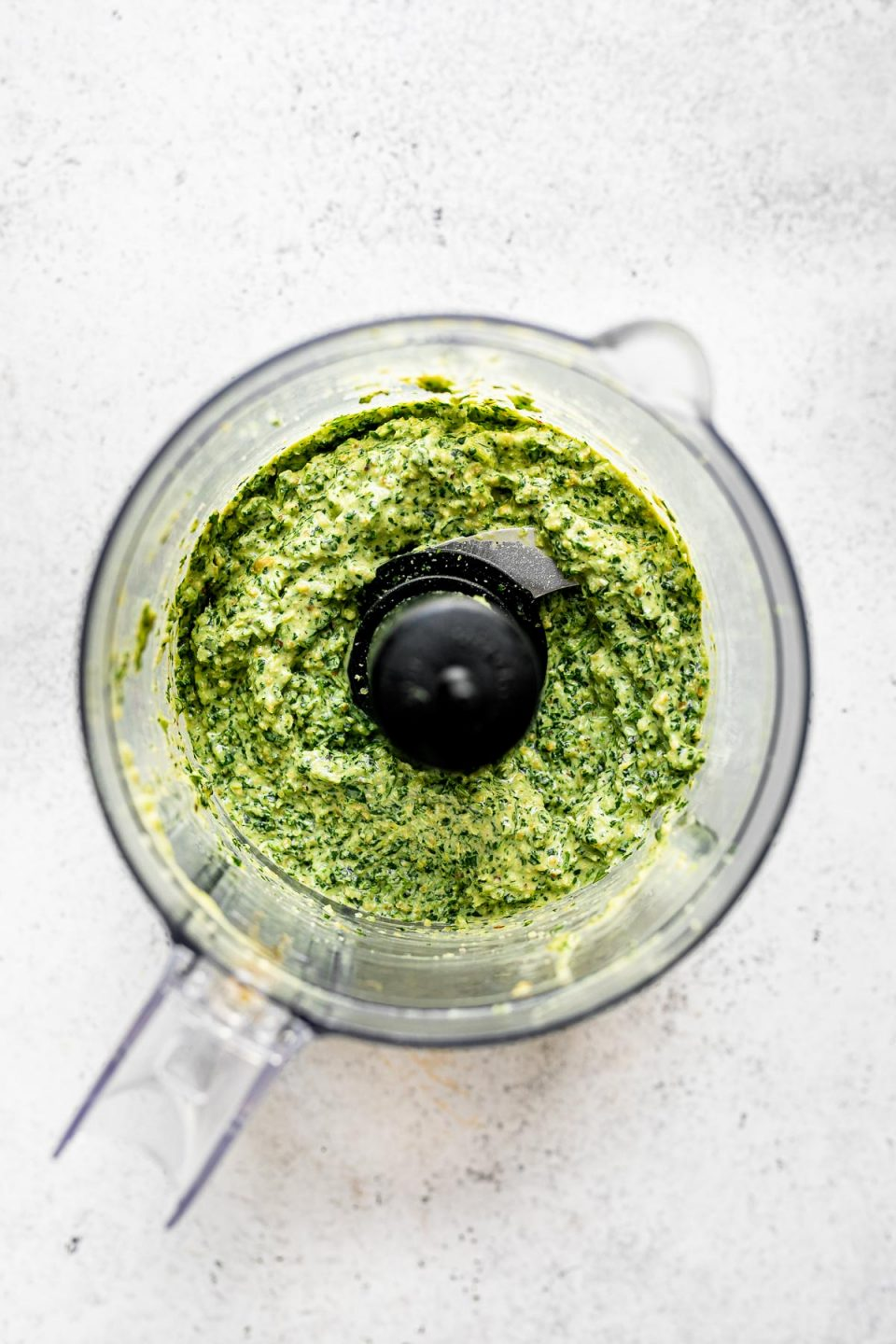 Blended jalapeño pesto in a food processor carafe, atop a light gray & white surface.