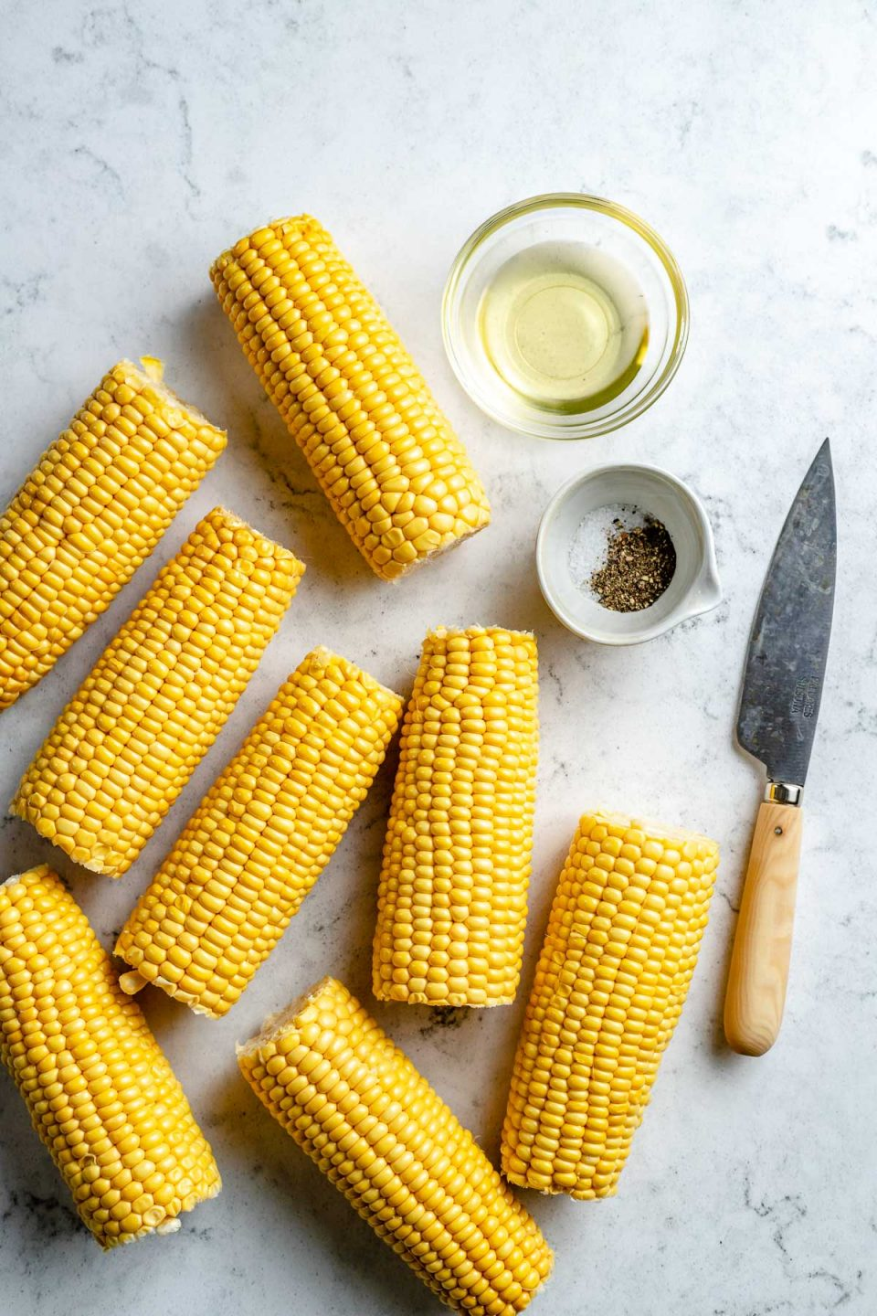 Grilled corn ingredients arranged on a white & grey marble surface - eight pieces of sweet corn, avocado oil, kosher salt, & ground black pepper. A pairing knife rests on the surface next to the ingredients.