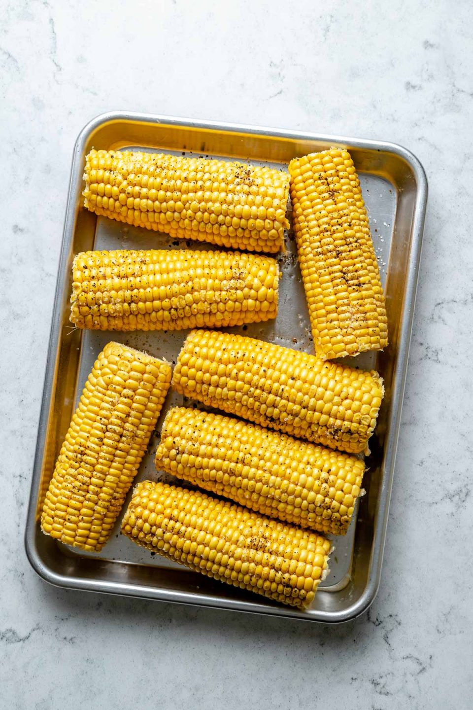 Multiple pieces of fresh & uncooked sweet corn seasoned with oil and ground black pepper lie on an aluminum baking sheet. The baking sheet sits on top of a white & gray marble surface.