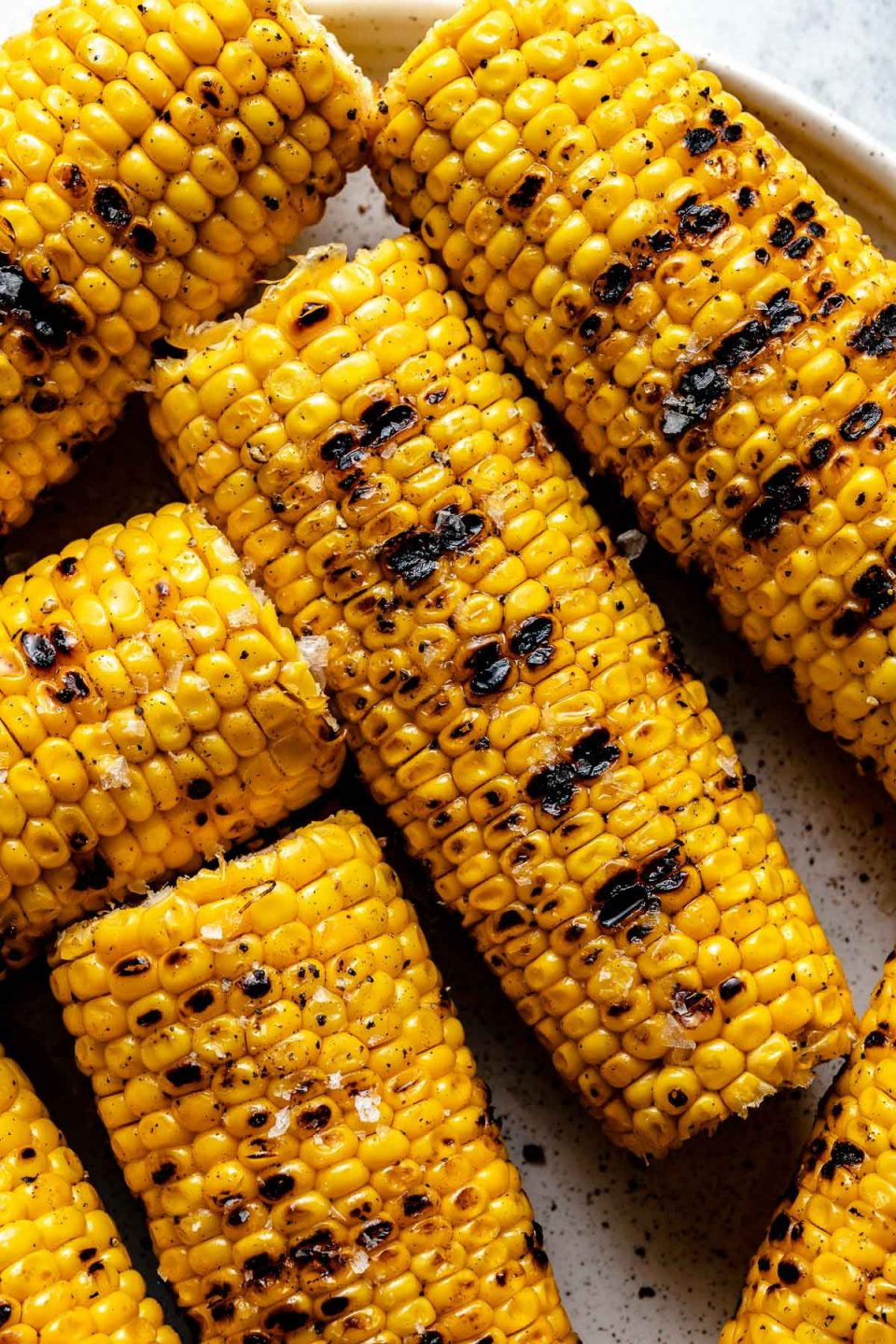Close up of grilled corn with char marks arranged on a white speckled ceramic plate. The corn is garnished with ground black pepper & kosher salt.
