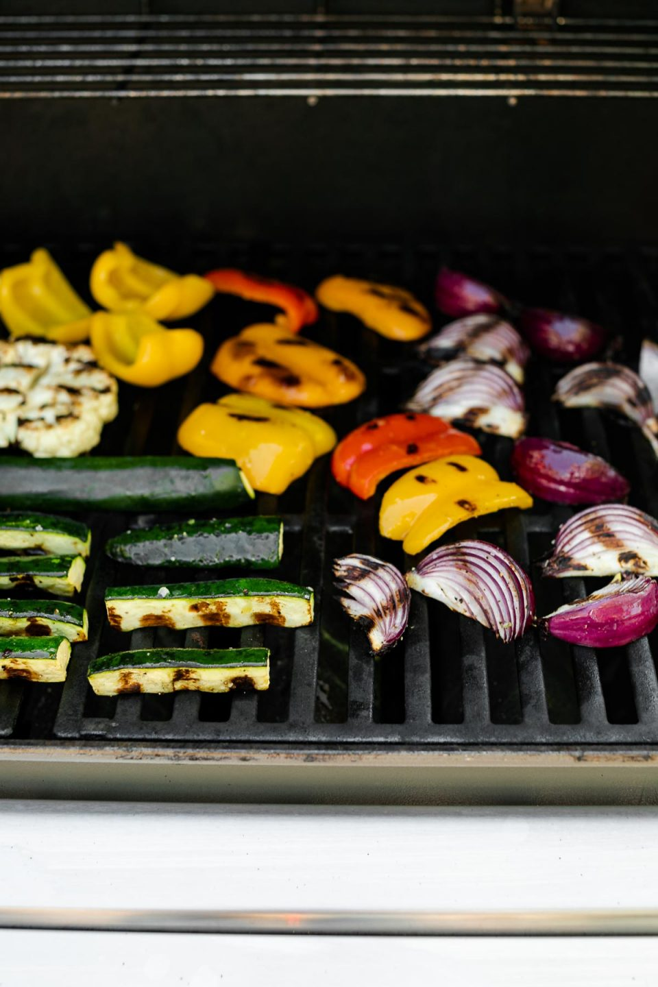 A straight on shot of a variety of grilled veggies including grilled broccolini, grilled asparagus, grilled cauliflower, grilled zucchini, grilled onion, & grilled peppers that are being grilled on gas grill grates. Many of the veggies have grill marks on them after being flipped to the other side.