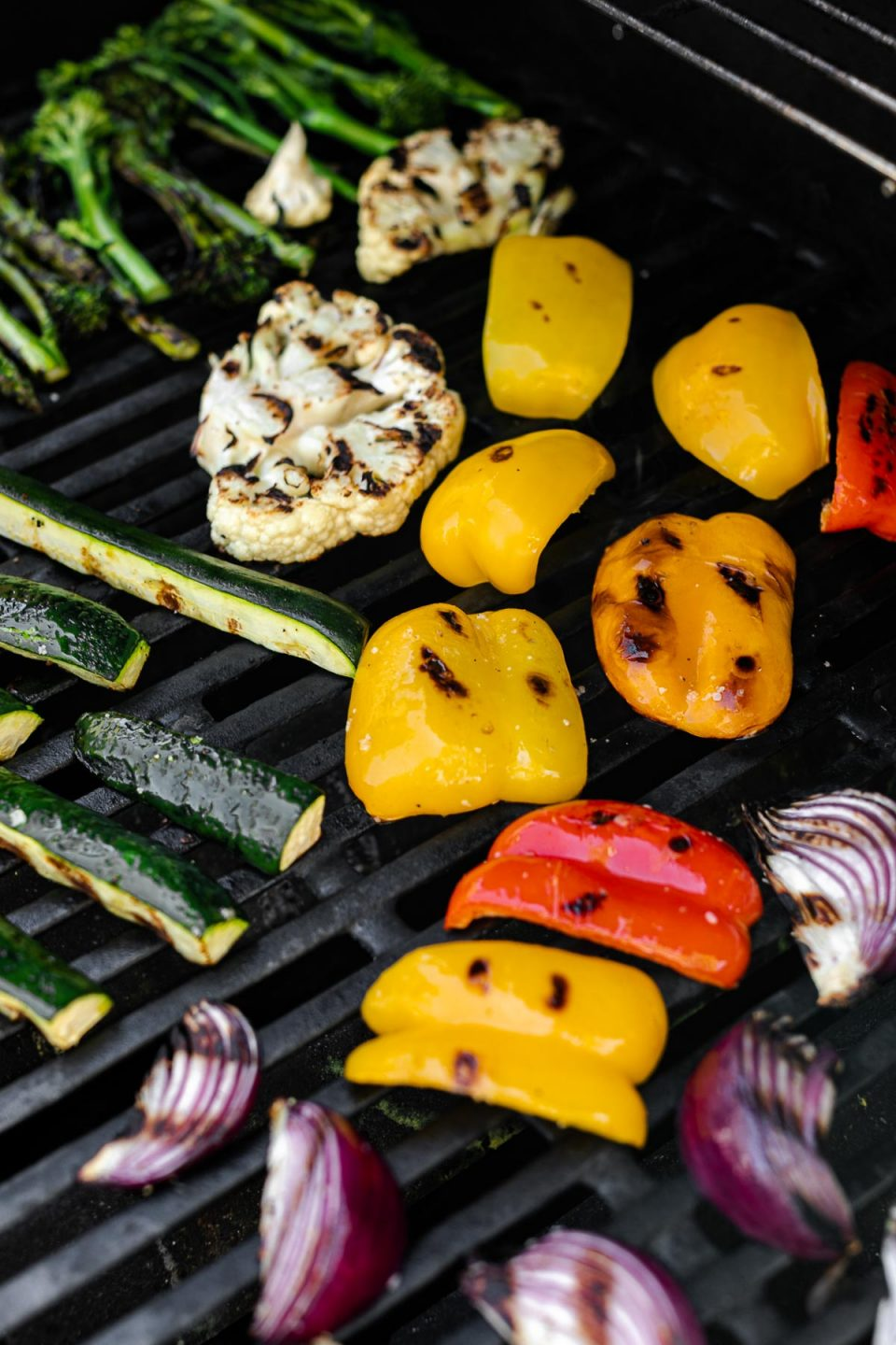 An angled shot of a variety of grilled veggies including grilled broccolini, grilled asparagus, grilled cauliflower, grilled zucchini, grilled onion, & grilled peppers that are being grilled on gas grill grates. Many of the veggies have grill marks on them after being flipped to the other side.