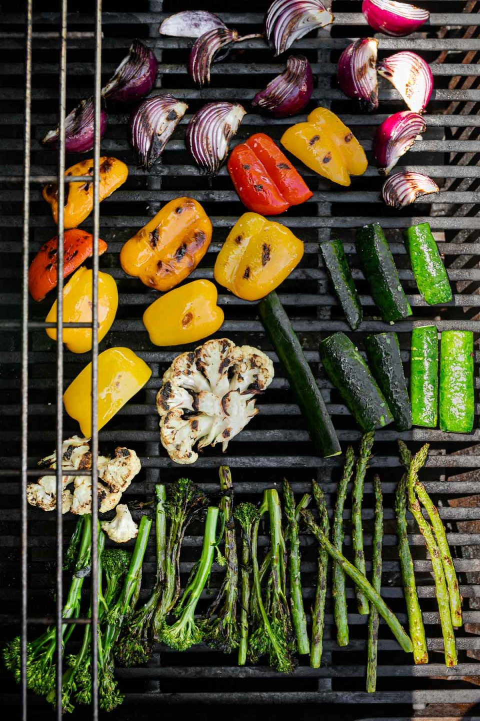 An overhead shot of a variety of grilled veggies including grilled broccolini, grilled asparagus, grilled cauliflower, grilled zucchini, grilled onion, & grilled peppers are being grilled on a gas grill grates. Many of the veggies have grill marks on them after being flipped to the other side.