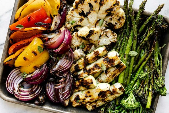 A variety of grilled veggies including grilled broccolini, grilled asparagus, grilled cauliflower, grilled zucchini, grilled onion, & grilled peppers on a aluminum baking sheet. The baking sheet rests on a white & gray marble surface.