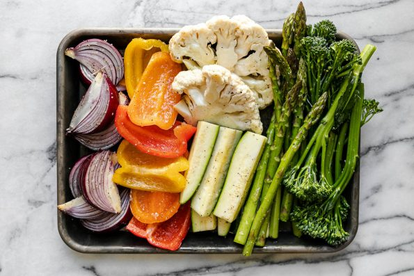 A variety of veggies including broccolini, asparagus, cauliflower, zucchini, onion, & peppers on a aluminum baking sheet. The baking sheet rests on a white & gray marble surface.