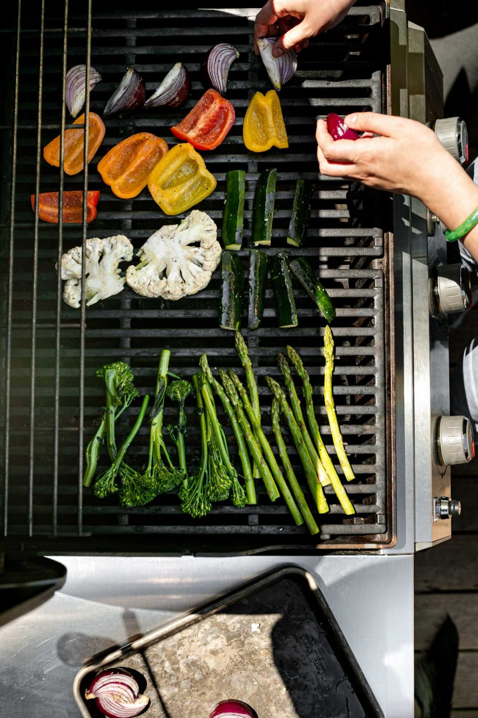 An overhead shot of a woman's hands placing a variety of raw veggies on top of gas grill grates for grilling. These veggies include broccolini, asparagus, cauliflower, zucchini, onion, & peppers. A aluminum baking sheet sits on the shelf to the left of the grill with additional onions ready to be placed on the grates.