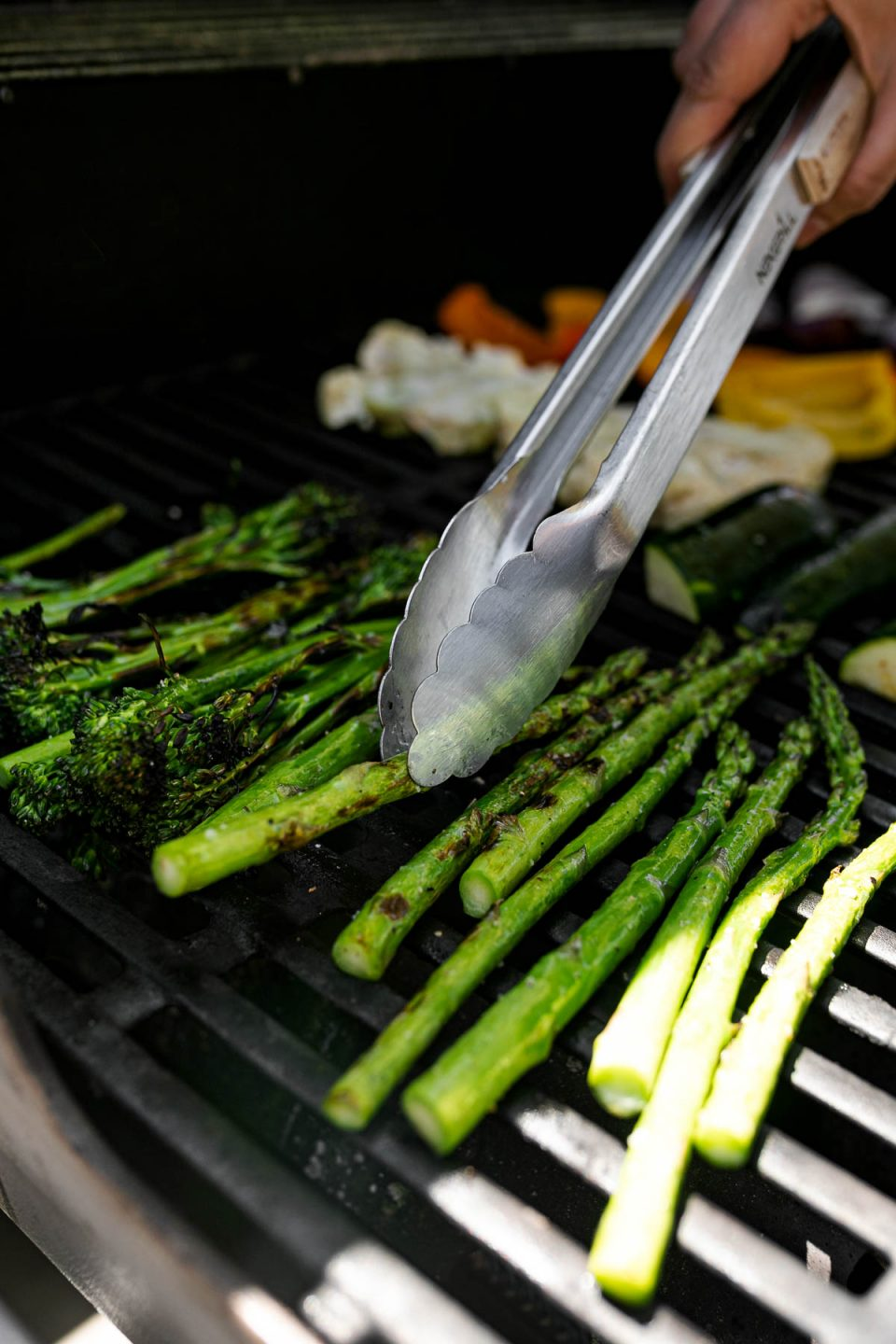 An angled shot of a variety of grilled veggies including grilled broccolini, grilled asparagus, grilled cauliflower, grilled zucchini, grilled onion, & grilled peppers that are being grilled on gas grill grates. A woman's hand holds a pair of tongs that are picking up a stalk of grilled asparagus & rotating it on the grill grates. Many of the veggies have grill marks on them after being flipped to the other side.
