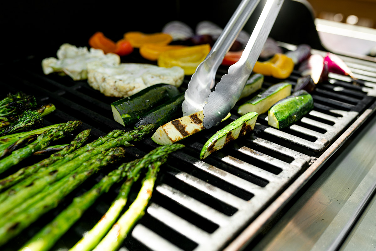 An angled shot of a variety of grilled veggies including grilled broccolini, grilled asparagus, grilled cauliflower, grilled zucchini, grilled onion, & grilled peppers that are being grilled on gas grill grates. A pair of tongs is picking up a grilled zucchini plank & it flipping it over on the grill to grill the opposite side. Many of the veggies have grill marks on them after being flipped to the other side.