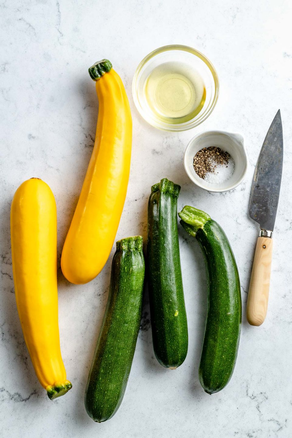 Grilled zucchini and yellow squash ingredients arranged on a white & grey marble surface - zucchini and yellow squash, avocado oil, kosher salt, & ground black pepper. A pairing knife rests on the surface next to the ingredients.