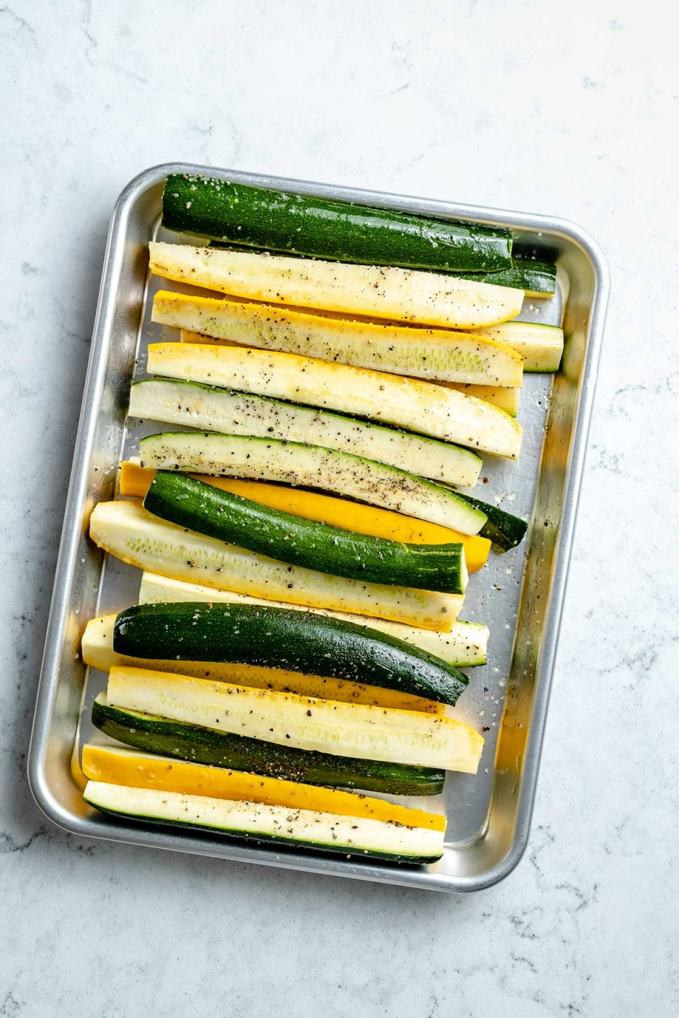 Fresh & raw zucchini and yellow squash spears seasoned with avocado oil, kosher salt, & ground black pepper arranged on an aluminum baking sheet. The baking sheet sits on top of a white & gray marble surface.