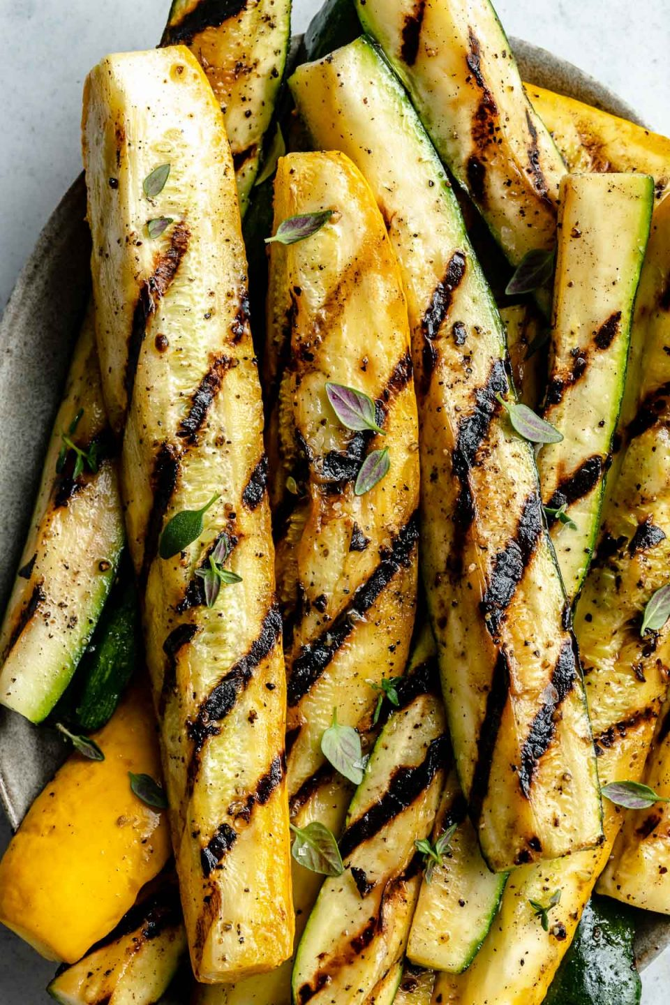A close up of grilled slices of zucchini and yellow squash spears with char marks arranged on a brown ceramic platter. The grilled zucchini and yellow squash is garnished with kosher salt, ground black pepper, & fresh herbs. The platter sits on top of a white & gray marble surface.