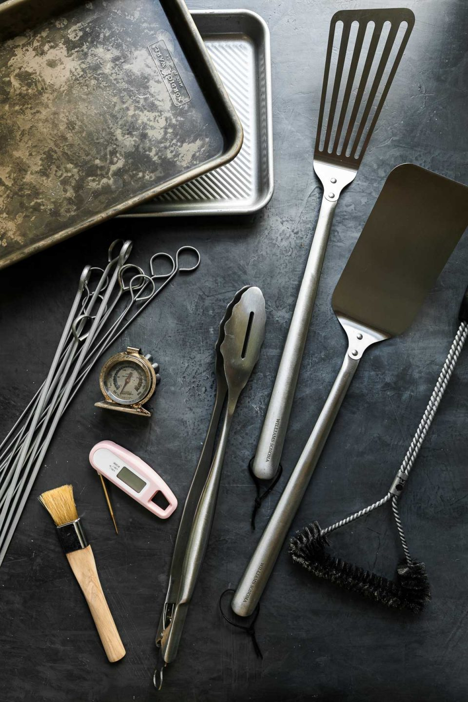 Grill tools arranged on a black surface: quarter sheet pans, stainless steel skewers, oven thermometer, instant read thermometer, pastry brush, grill tongs, grill spatula, grill brush.