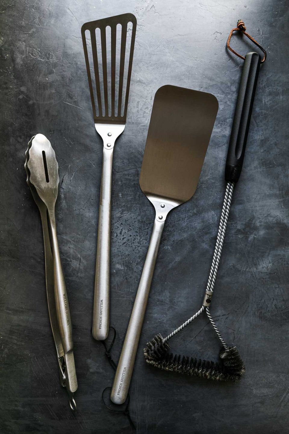Grill tools arranged on a black surface: grill tongs, grill spatulas, grill brush.