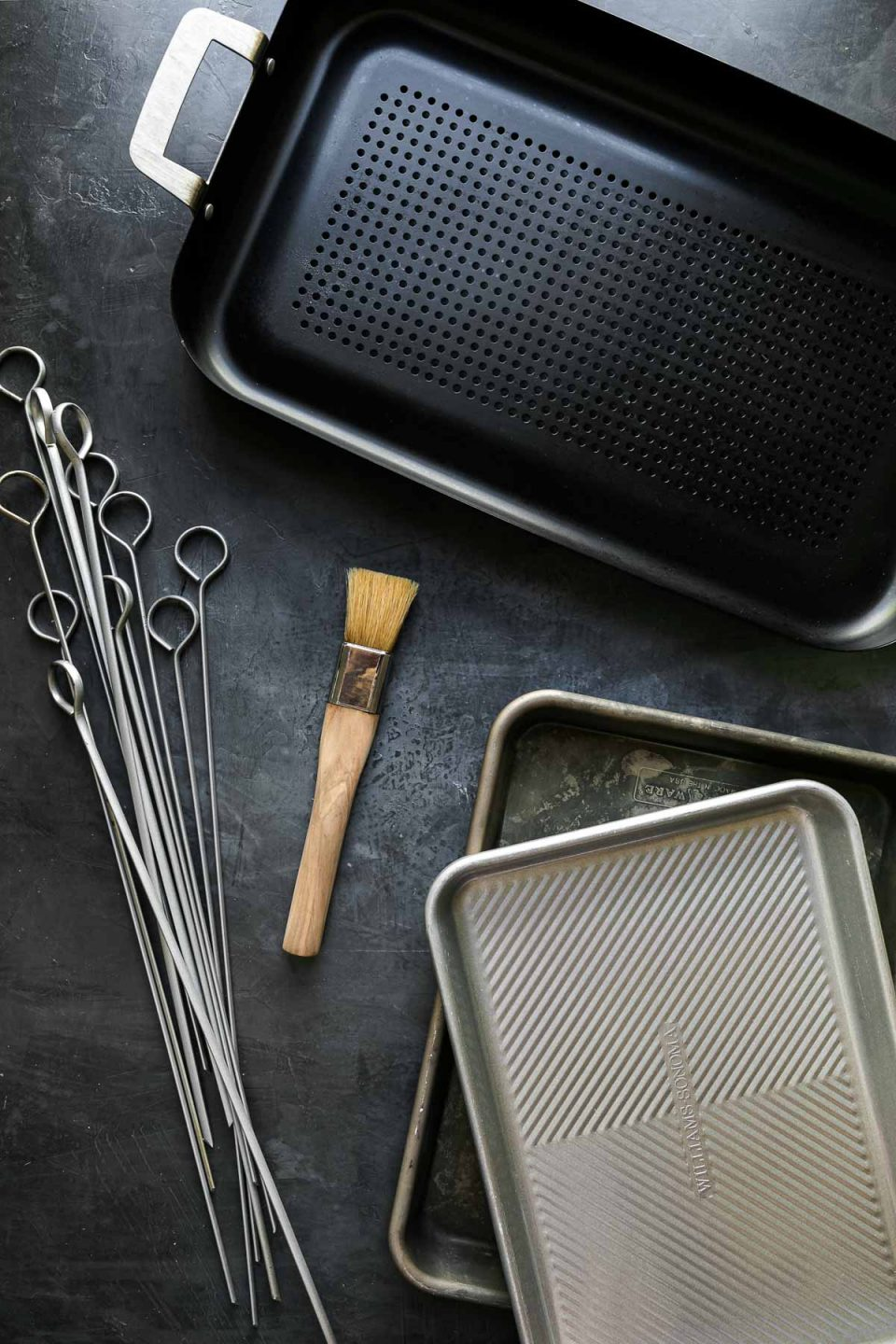 Grill tools arranged on a black surface: quarter sheet pans, stainless steel skewers, pastry brush, & a grill pan.