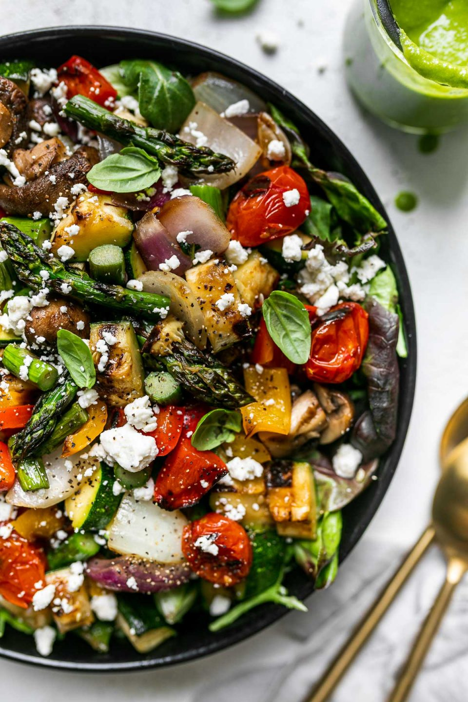 Chopped grilled vegetable salad garnished with cheese in a large black serving bowl atop a gray linen napkin on a white surface. 2 gold serving spoons, a jar of lemon basil vinaigrette, cheese crumbles, & loose basil leaves surround the serving bowl.