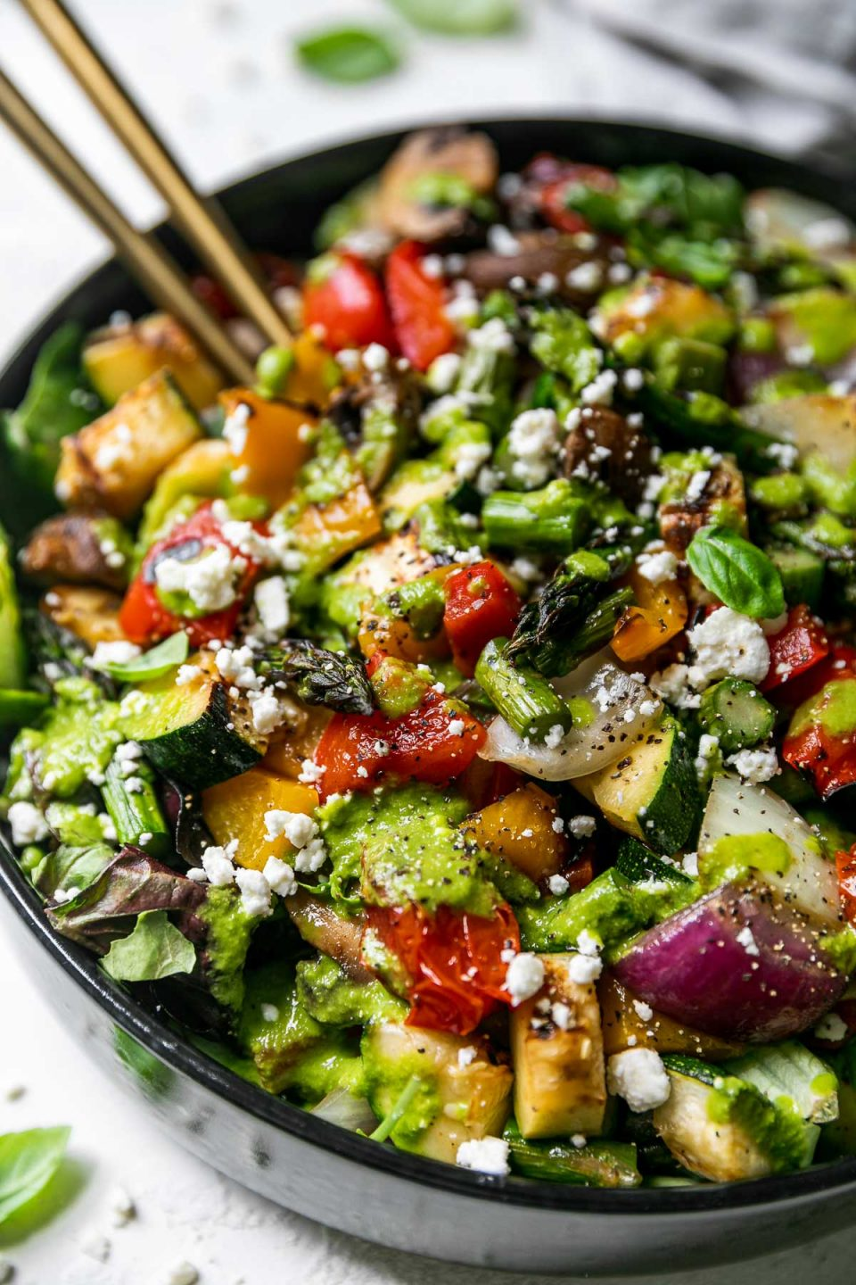 Side angle of chopped grilled vegetable salad in a large black serving bowl atop a light gray surface. 2 gold serving spoons are nestled into the chopped vegetable salad. Fresh basil leaves & a jar of lemon basil vinaigrettes surround the serving bowl.