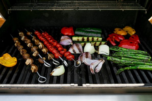 A straight on shot of a variety of grilled veggies including grilled asparagus, grilled zucchini, grilled onion, grilled bell peppers, grilled cherry tomatoes on skewers, & grilled mushrooms on skewers are being grilled on gas grill grates. Many of the veggies have grill marks on them after being flipped to the other side