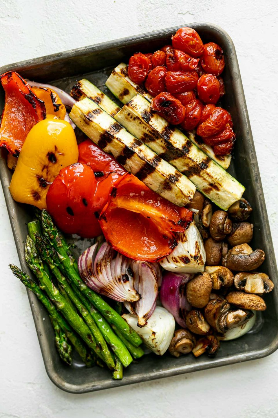 A variety of grilled veggies including grilled asparagus, grilled peppers, grilled onion, grilled mushrooms, grilled tomatoes, & grilled zucchini on an aluminum baking sheet. The baking sheet rests on a white surface.