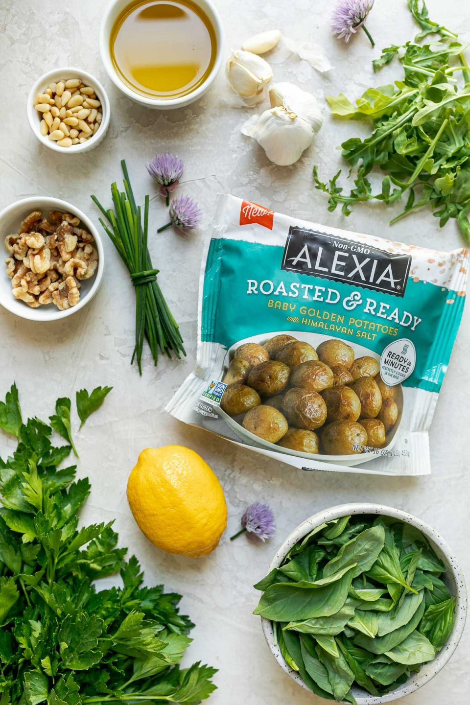 Green goddess pesto potato salad ingredients arranged on a white surface – Alexia Roasted & Ready Baby Golden Potatoes, extra virgin olive oil, baby arugula, chives, lemon zest & juice, garlic, walnuts, pine nuts, basil leaves, parsley leaves, kosher salt, & crushed red pepper flakes.