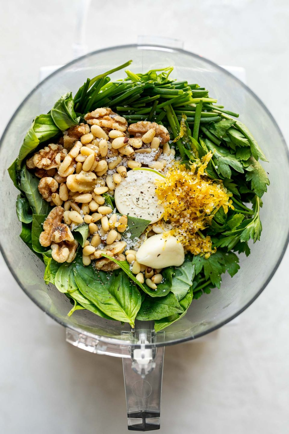 Green goddess pesto ingredients arranged in a food processor – basil leaves, parsley leaves, chives, lemon zest & juice, garlic, walnuts, pine nuts, extra virgin olive oil, & kosher salt. The food processor carafe sits atop a white surface.