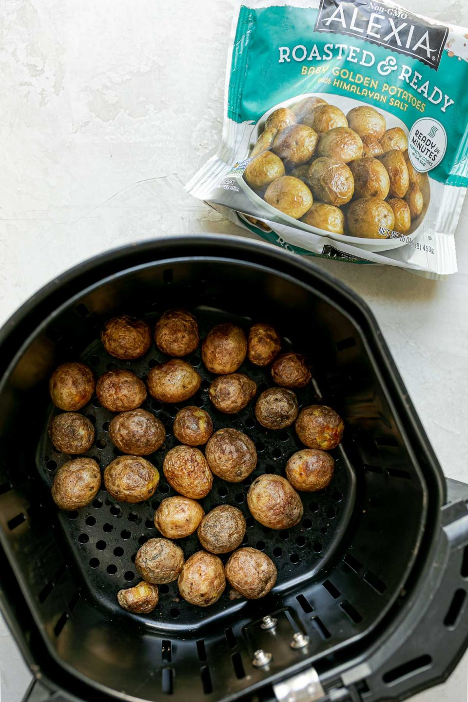 Alexia Ready & Roasted Baby Golden Potatoes inside an Air Fryer basket. The air fryer sits on top of a white surface. A bag of Alexia Roasted & Ready Baby Golden Potatoes sits next to the air fryer basket.
